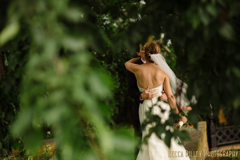 bride and groom kiss hidden by trees st paul