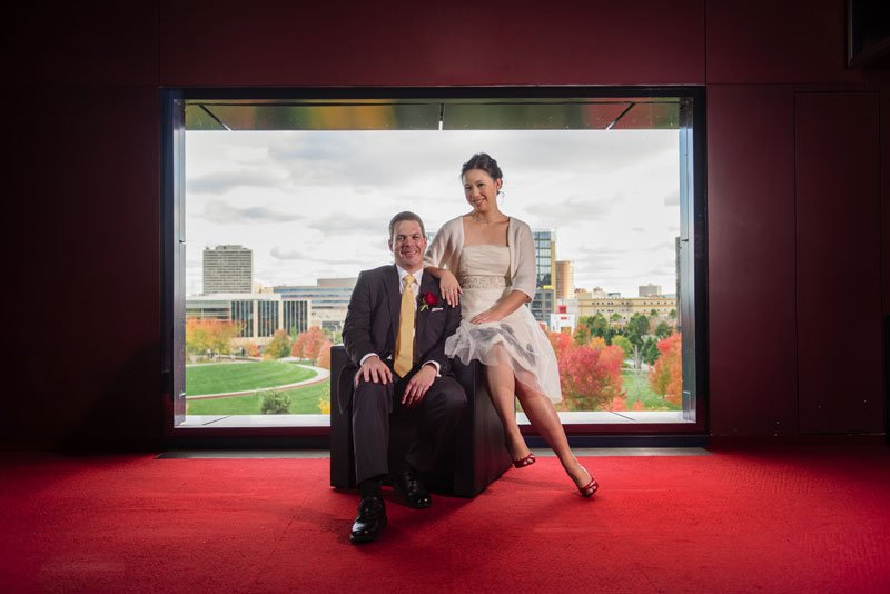 bride and groom in red lobby of guthrie theater