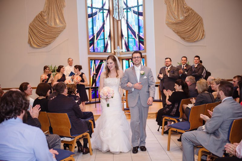 bride and groom walk down aisle after madison wedding ceremony at Church of the living Christ
