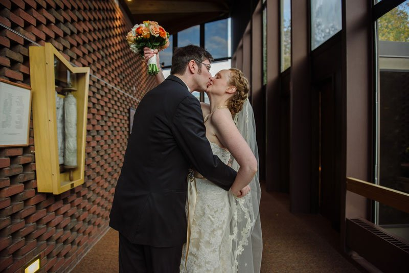 bride and groom kiss in lobby of weyerhaeuser chapel macalester college, mn history center wedding