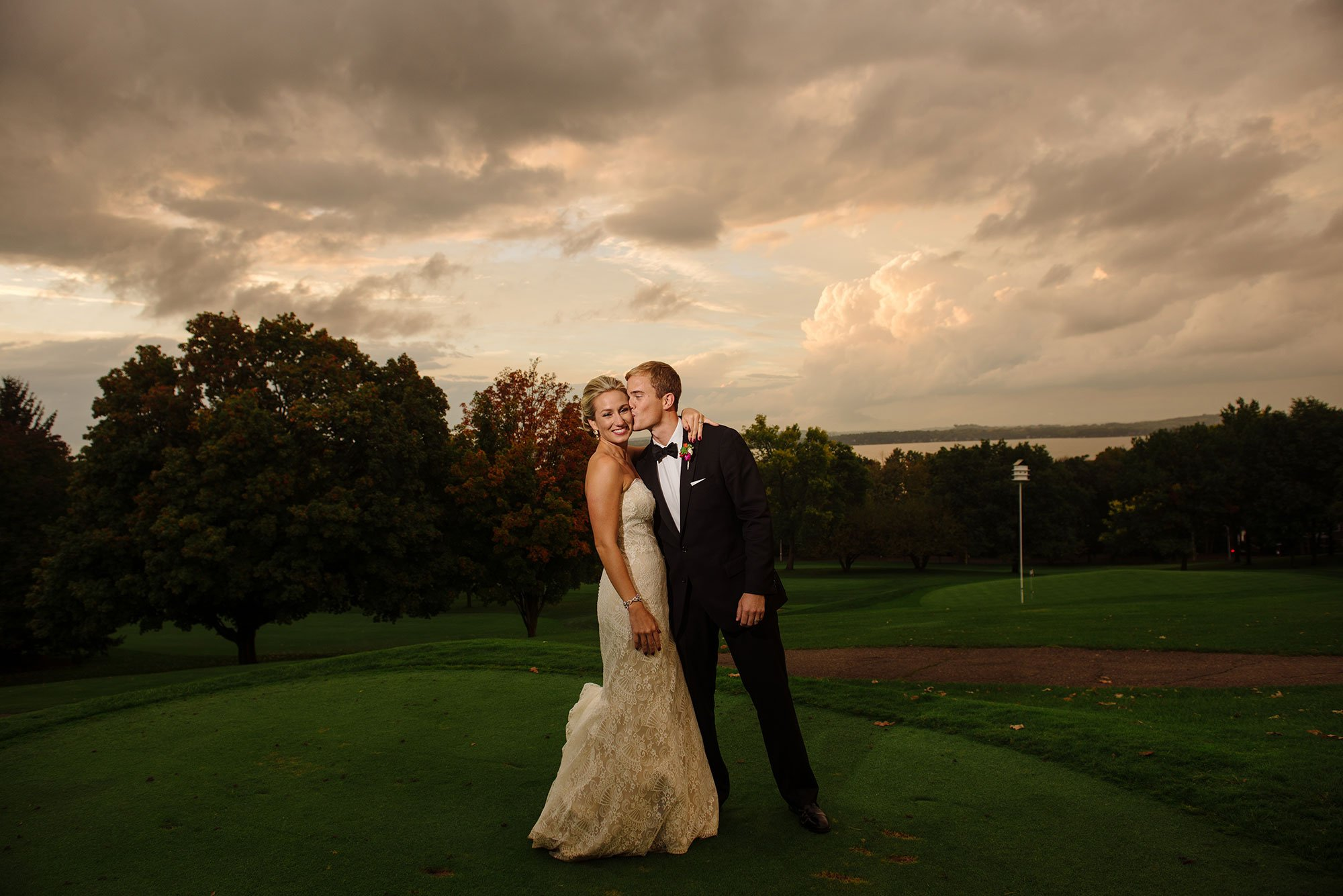 bride and groom with storm clouds behind them in front of blackhawk country club madison wi
