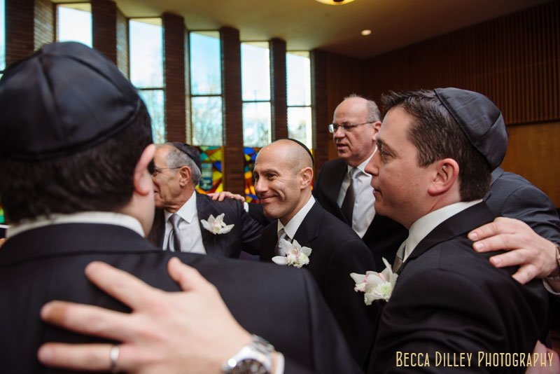 groom surrounded by men enters to sign ketubah at Beth El Synagogue in St Louis Park MN