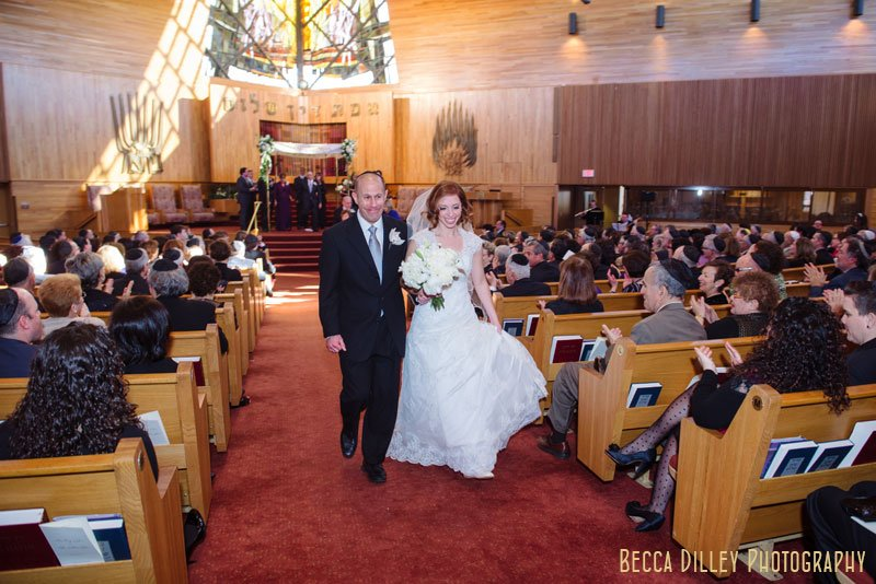 bride and groom walk down aisle after wedding at Beth El Synagogue in St Louis Park MN