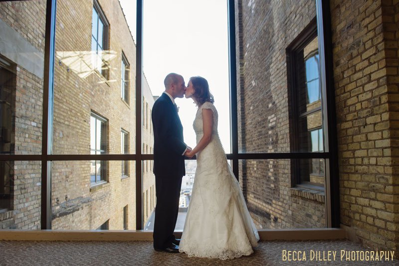bride and groom in front of window at IMS Design Center wedding reception
