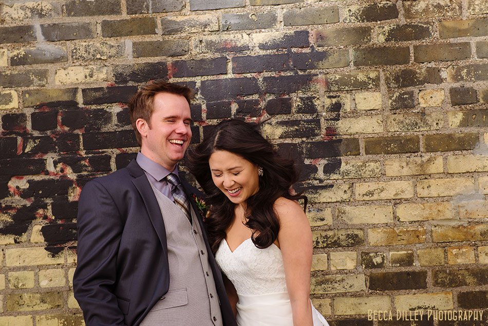 bride and groom laugh in front of brick wall at Varsity Theater wedding Minneapolis