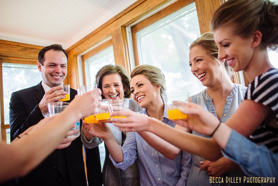 bride toasts with bridesmaids before getting ready for wedding