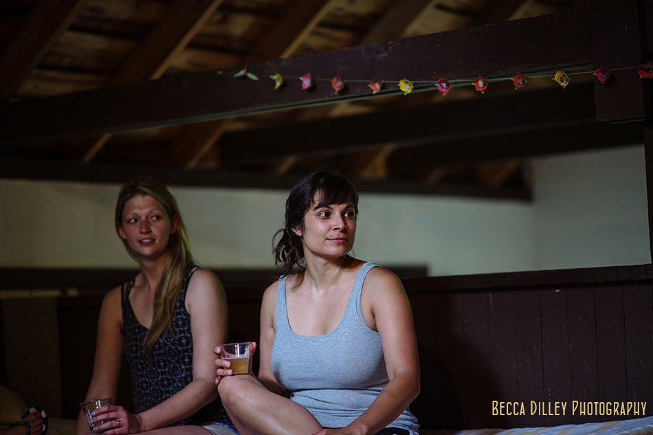friend sits with drink in dark barn space of wisconsin wedding