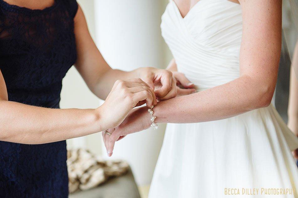 bridesmaid puts on brides bracelet minneapolis