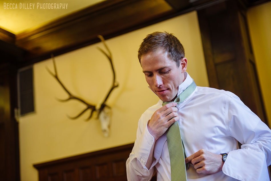 groom adjusting tie with antlers at minneapolis club wedding