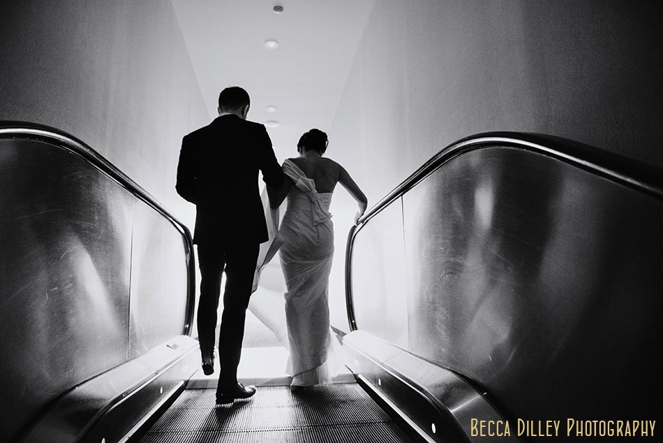 bride and groom on escalator at guthrie theater
