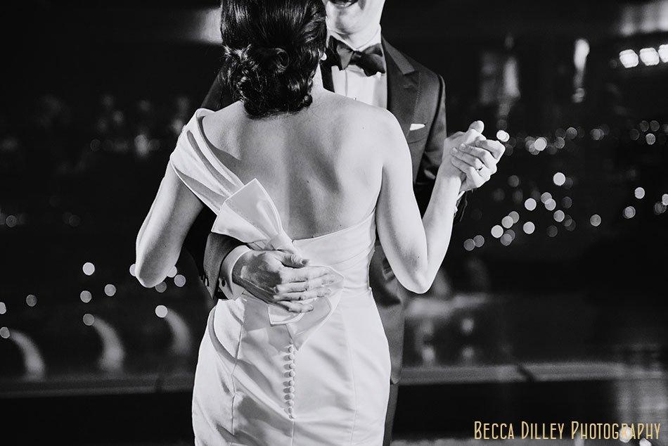 groom has arm around brides waist for first dance