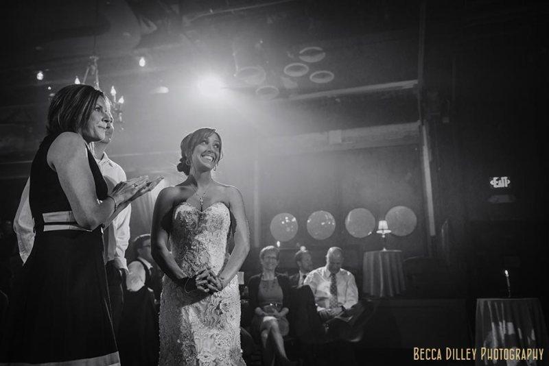 bride looks on during toasts minneapolis wedding photographer varsity theater april mn