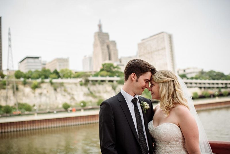 comfortable wedding photography couple on raspberry island with st paul skyline behind them