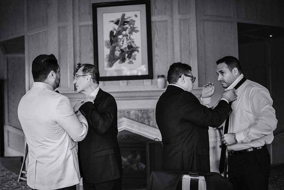 father of groom and groomsmen help put ties on each other at wayzata country club wedding