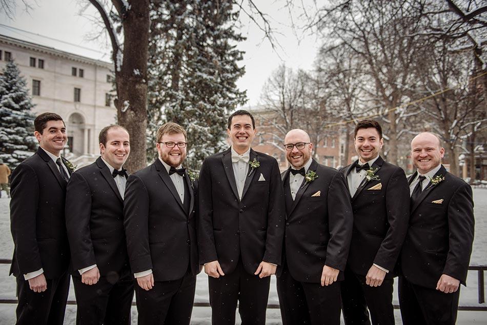 6 groomsment outside St Paul Hotel winter wedding mn