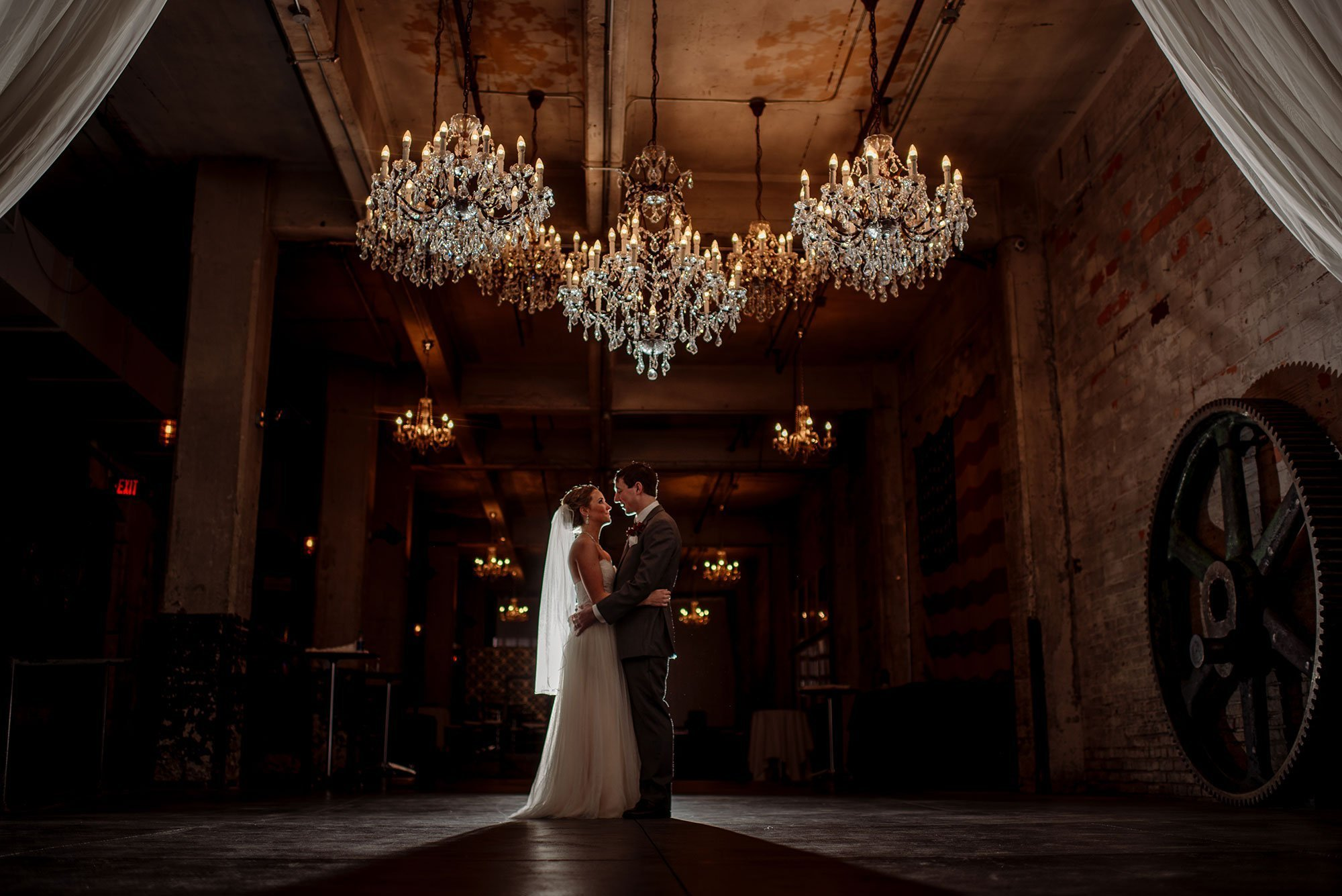 dramatic lighting Aria winter wedding couple under chandeliers