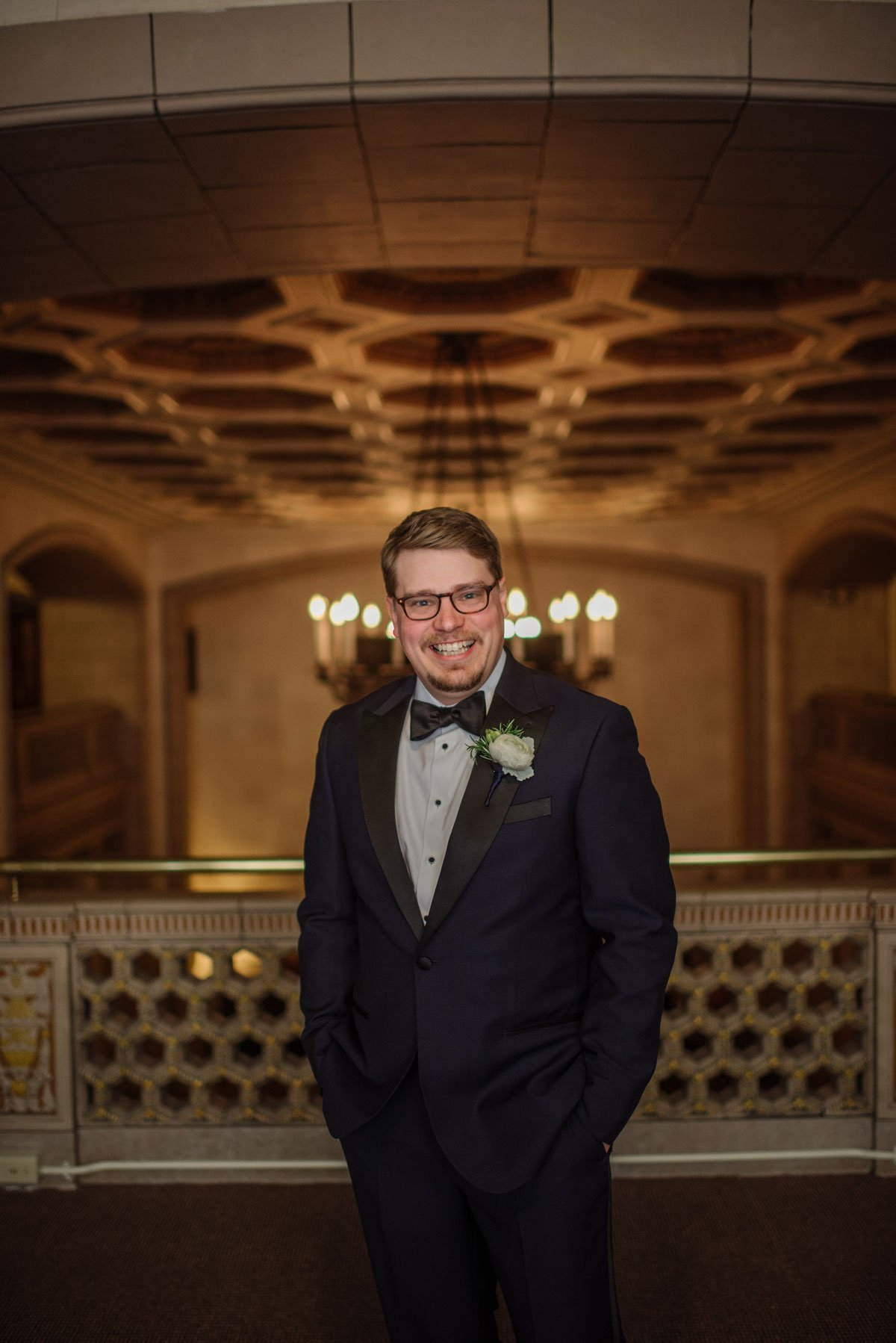 groom in upper balcony of hotel st paul althletic club for laughing formal portrait