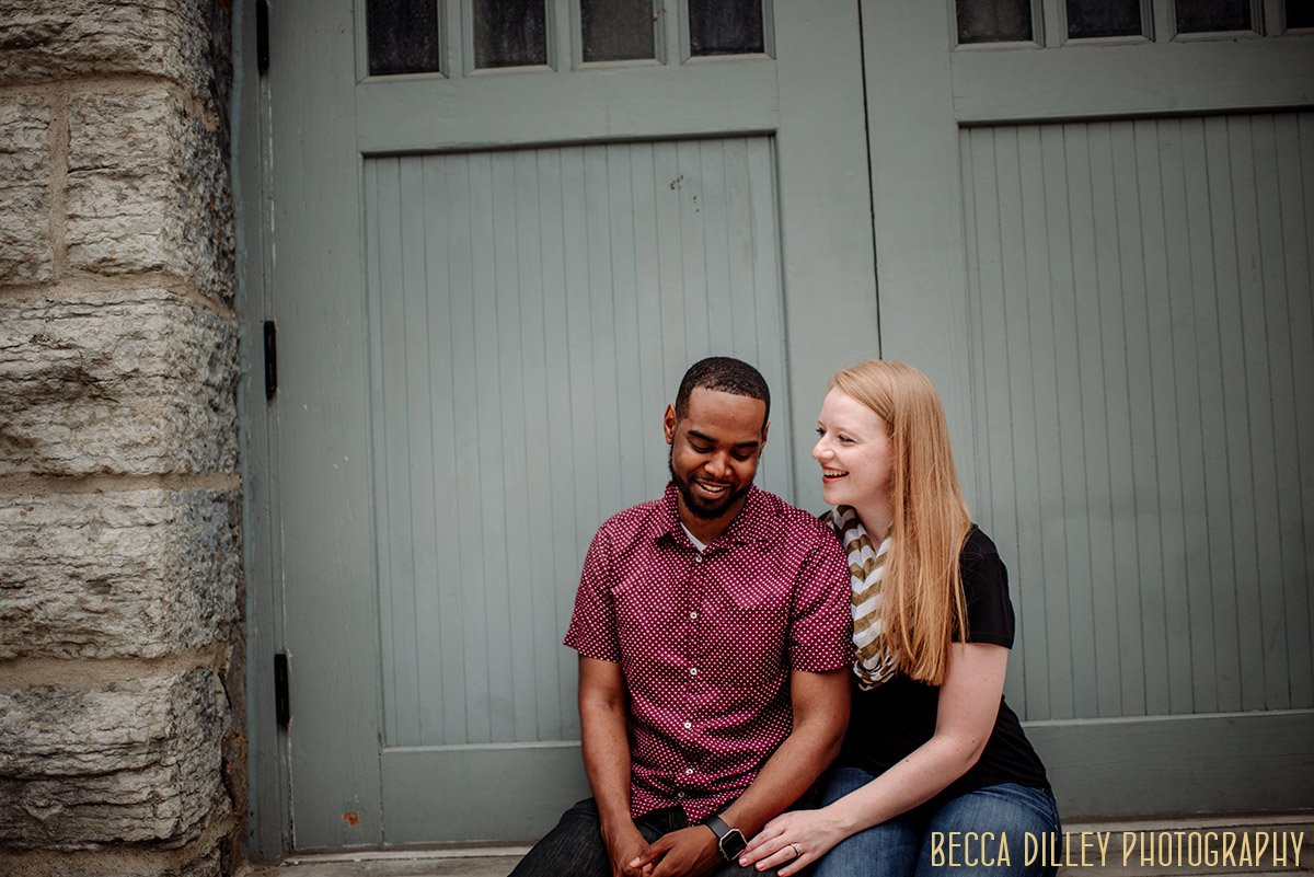 couple on stone bench in downtown minneapolis for engagmenet photos mixed