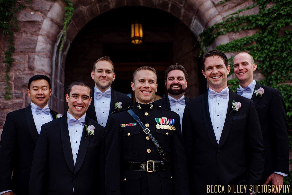 groom in military jacket and groomsmen stand on stairs of Van Dusen Mansion Wedding Minneapolis