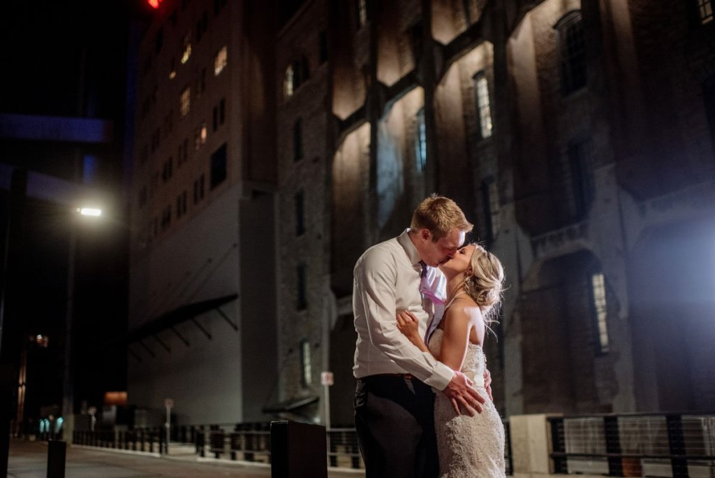 bride and groom kiss outside Machine shop wedding