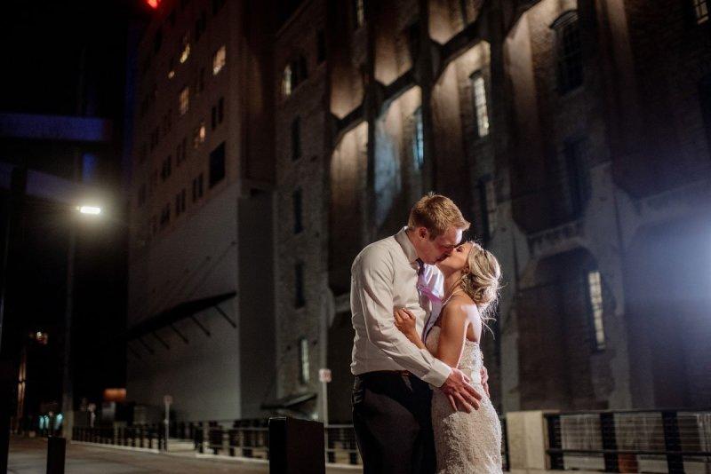 bride and groom kiss outside Machine shop wedding