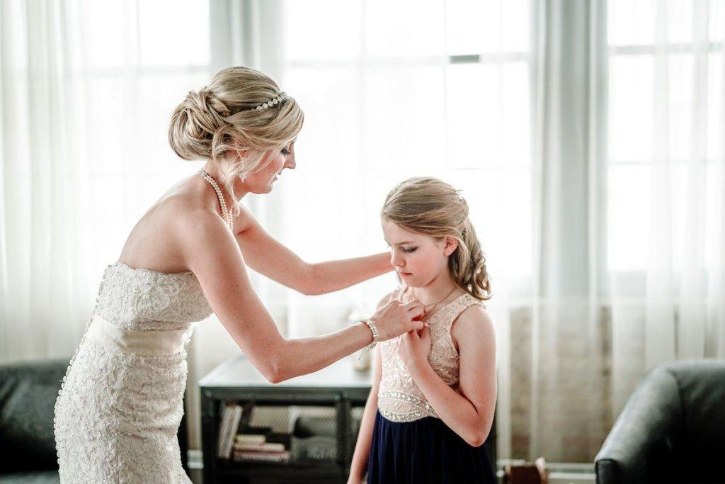 Bride adjusts necklace on junior bridesmaid before Machine shop wedding