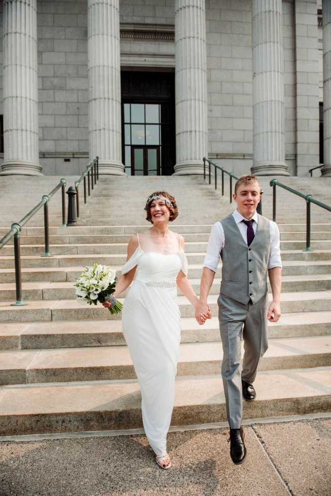 Couple walks down stairs of Minneapolis Institute of Art on wedding day