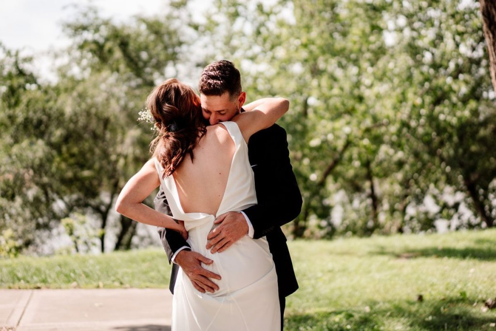couple embrace in minneapolis park before their summer wedding