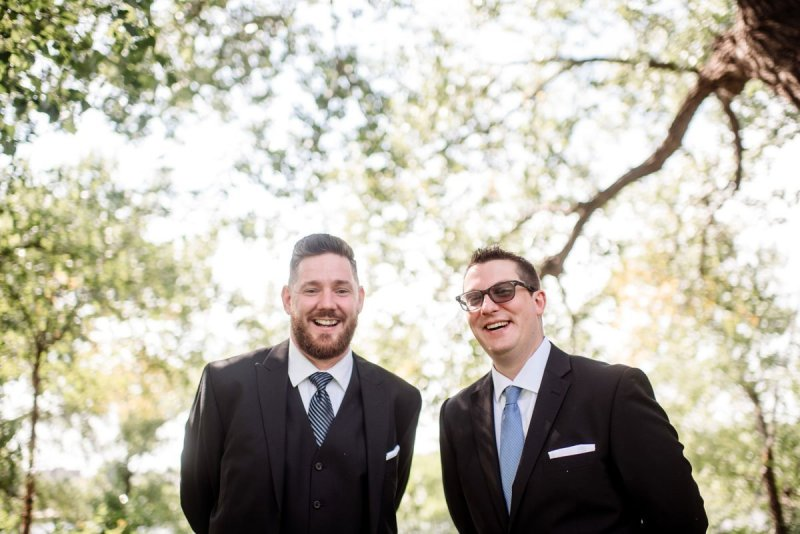groom and best man laugh together at minneapolis park before summer wedding