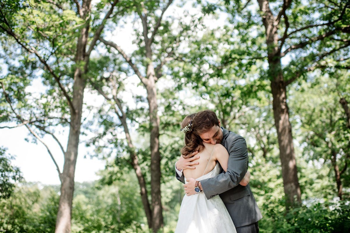 couple embrace under trees at silverwood park wedding mn
