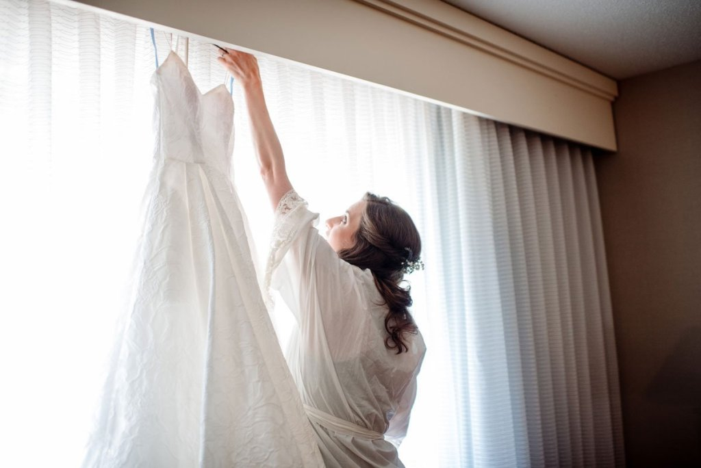 bride reaching for gown in hotel room minneapolis