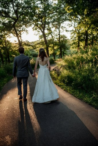 couple walking on sunlight path at silverwood park wedding mn