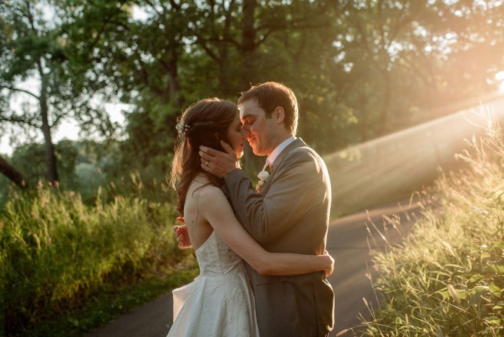 bride and groom kiss in sun light silverwood park wedding mn