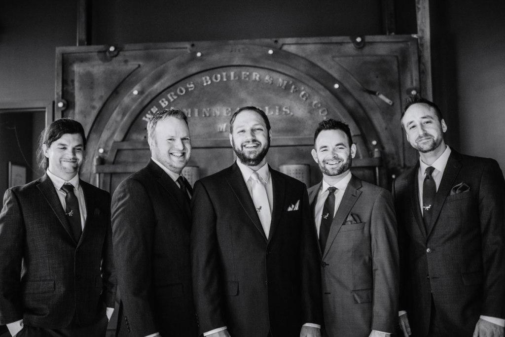 groom and groomsmen in front of iron door at solar arts