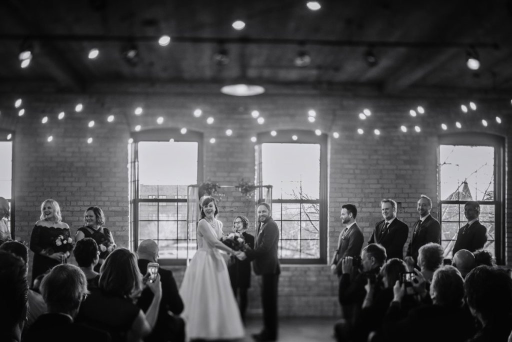 black and white photo of ceremony at solar arts in NE minneapolis with fairy lights and tilt shift lens