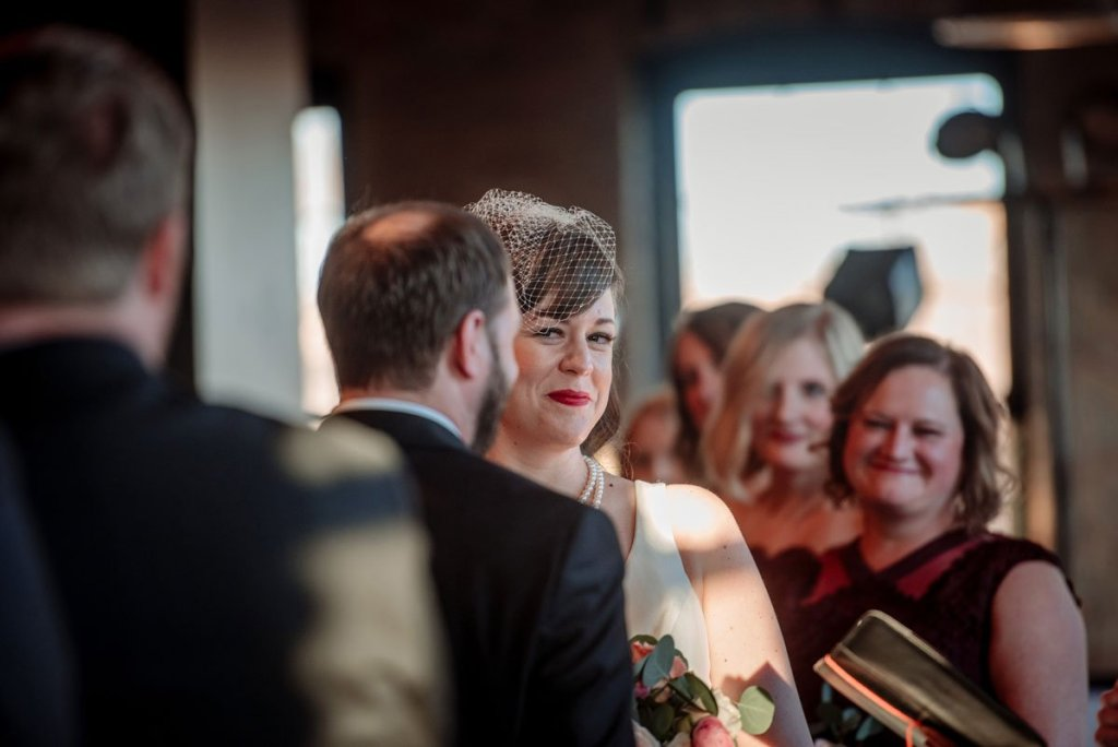 bride gives half smile during wedding ceremony at solar arts in ne minneapolis