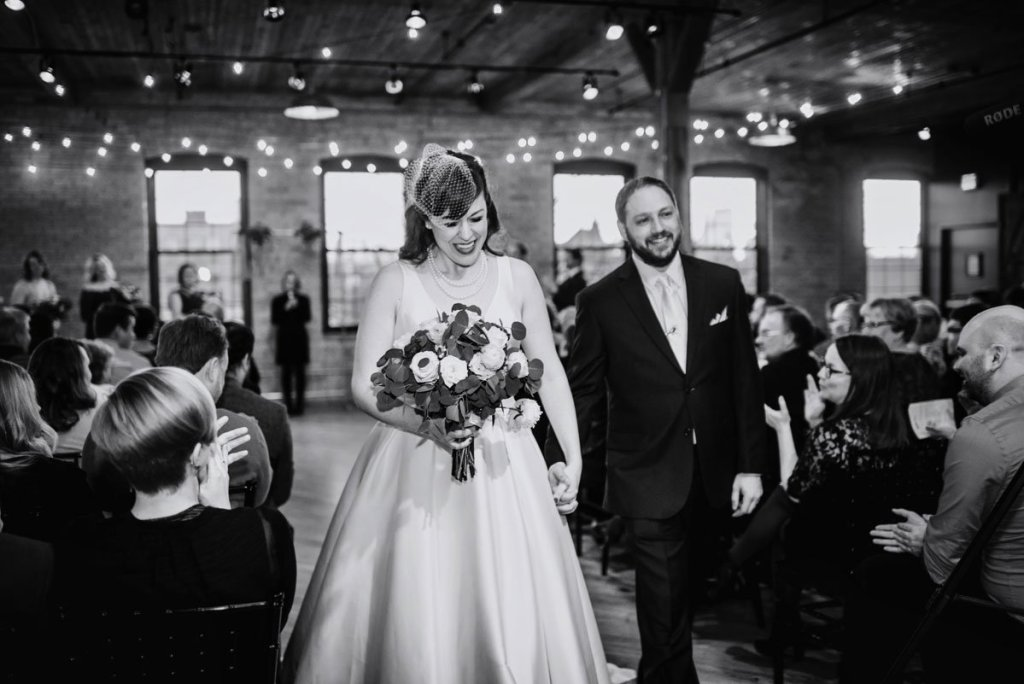 bride and groom walk down aisle after solar arts wedding photo in black and white