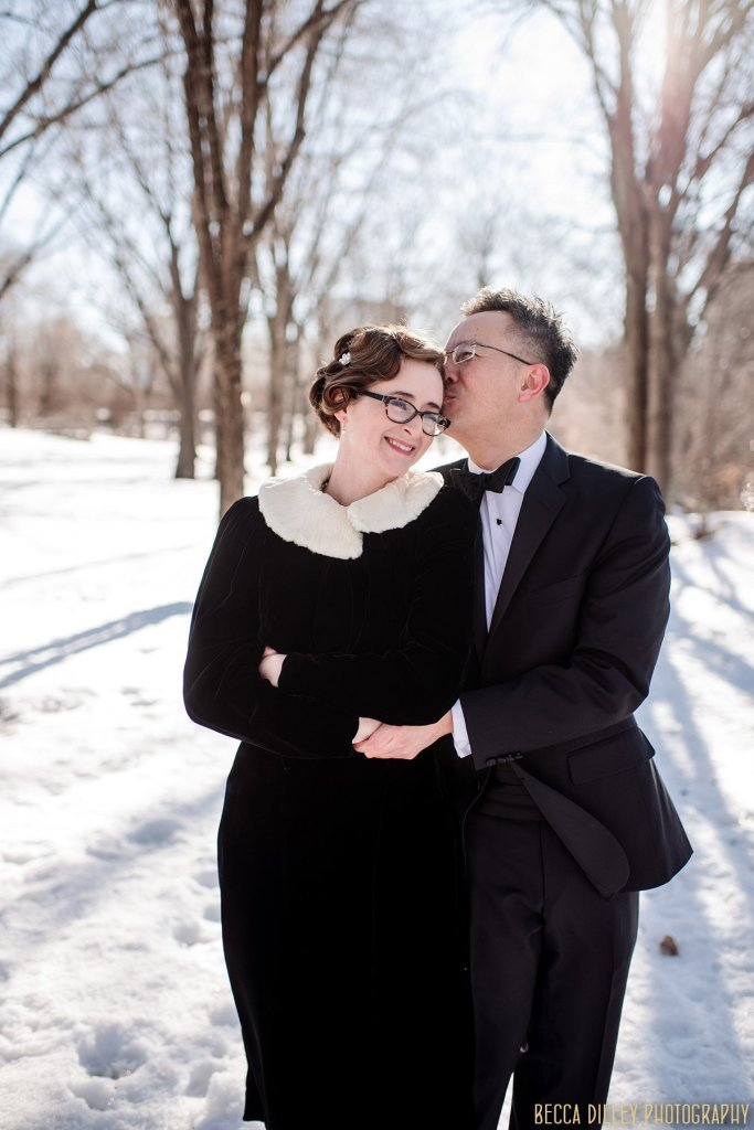 couple cuddle together in on snowy day in winter for elopement photos in minneapolis