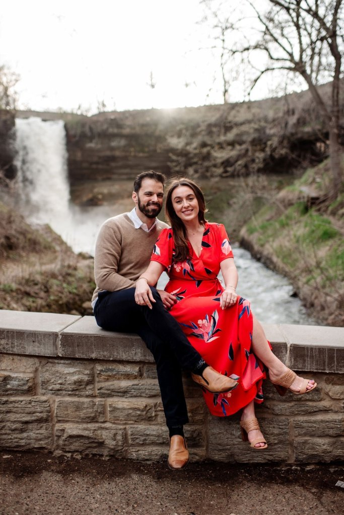 modern couple having fun at minnehaha falls for portraits by the waterfall in minneapolis summer