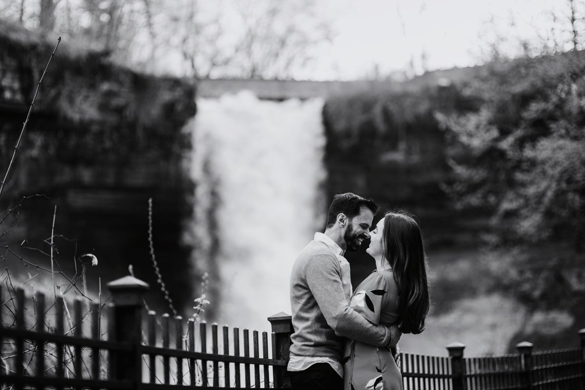 black and white couple having fun at minnehaha falls for portraits by the waterfall in minneapolis summer