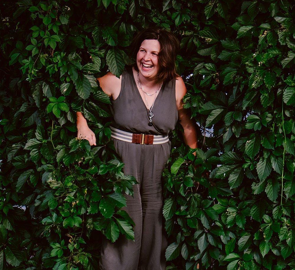 bio photo of Becca Dilley, minneapolis wedding photographer, hidding in trees