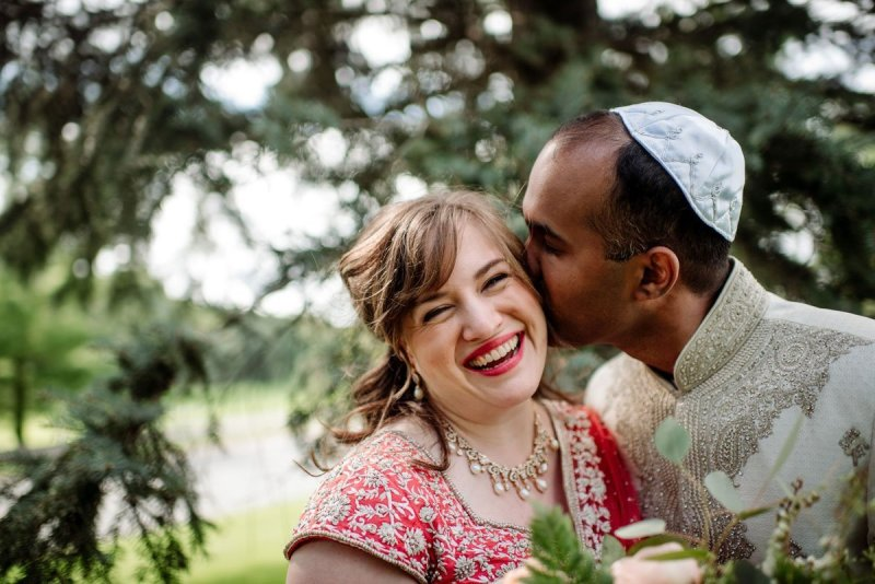 groom kisses bride on cheek outside she is wearing hindu sari