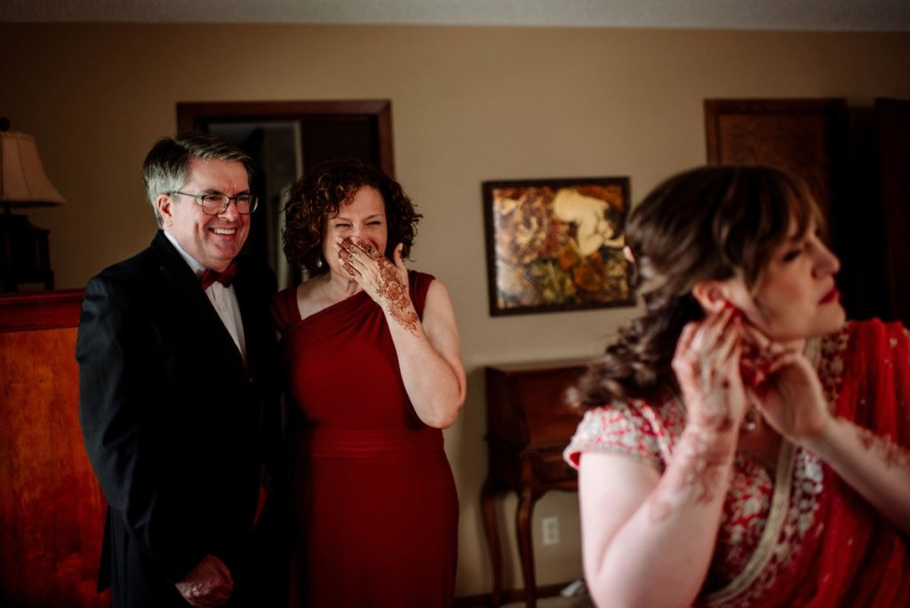 brides parents look on and cry as she puts on her earings before wedding