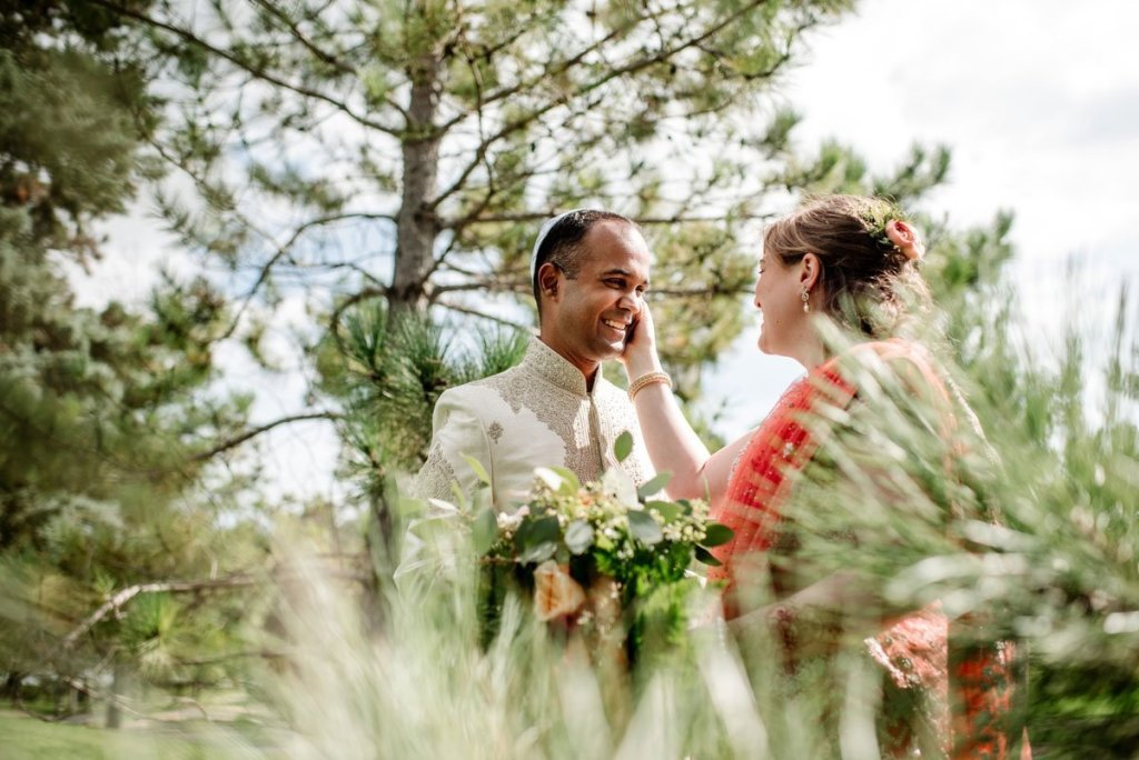 bride touches grooms face amidst pine trees