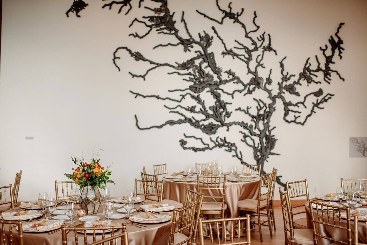gold themed reception tables set up at Weisman Art Museum