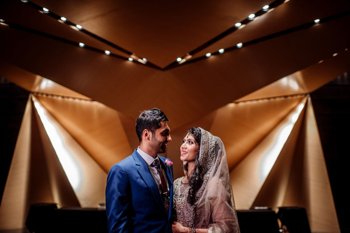 bride in pakistani sari and groom in navy suit with modern architecture of McNamara center Muslim Pakistani wedding in Minneapolis.
