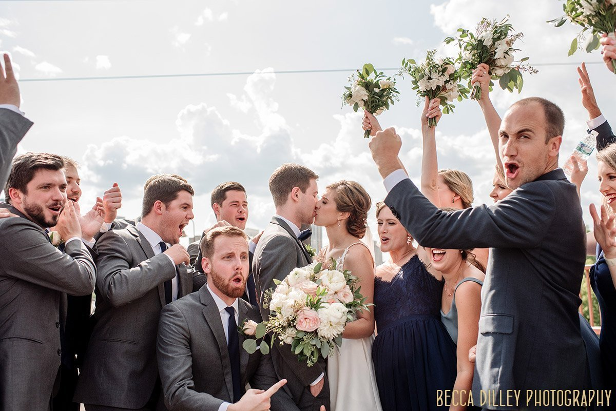 wedding party holds up flowers and surrounds couple with laughter in minneapolis portrait