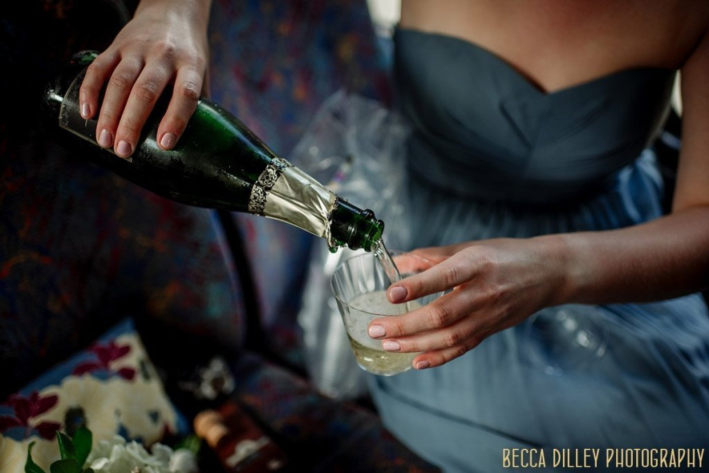 bridesmaid pours champagne