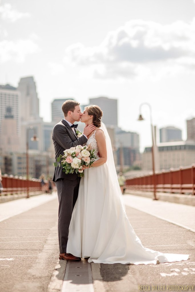 couple embrace on stone arch bridge in minneapolis