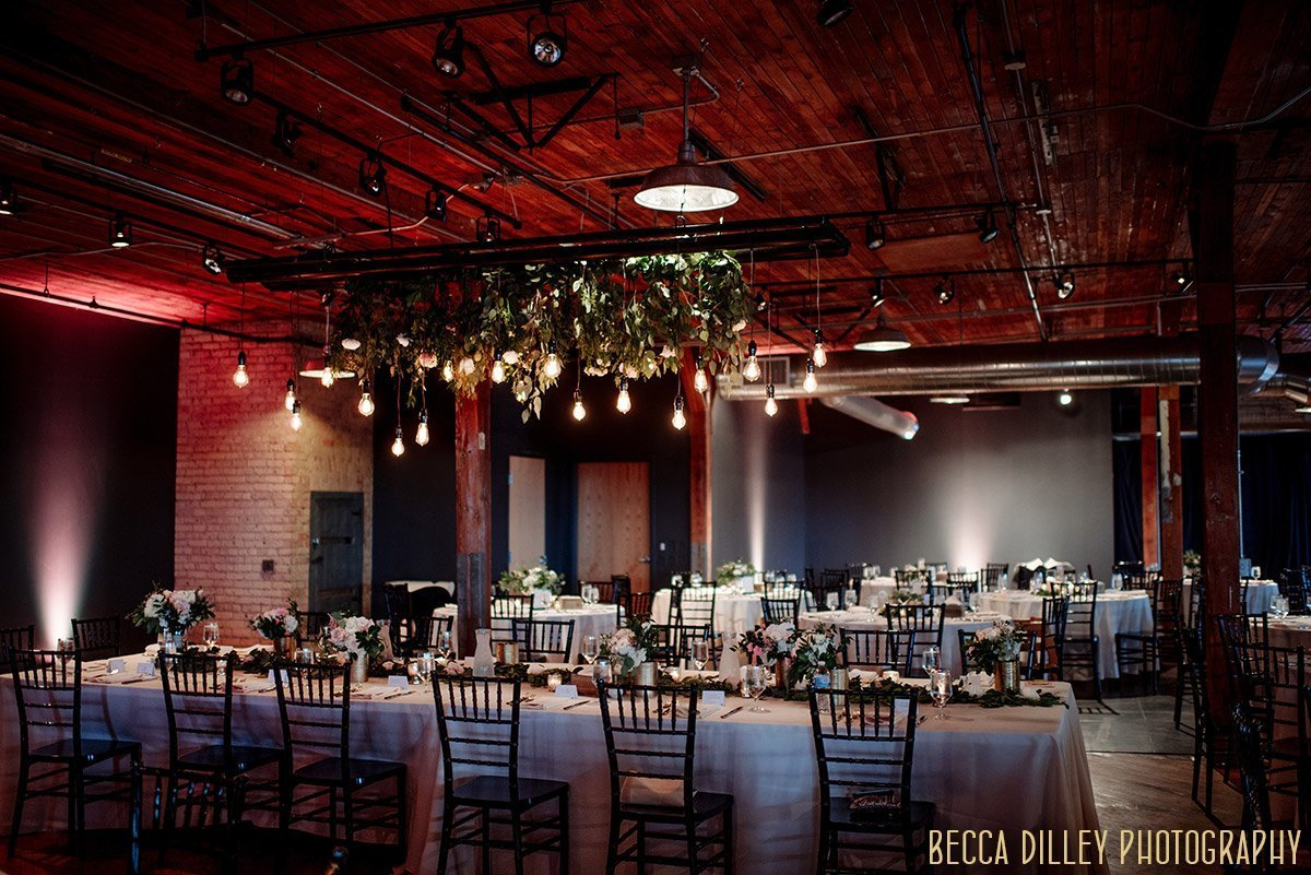 interior of solar arts wedding reception with tablesettings and hanging lights